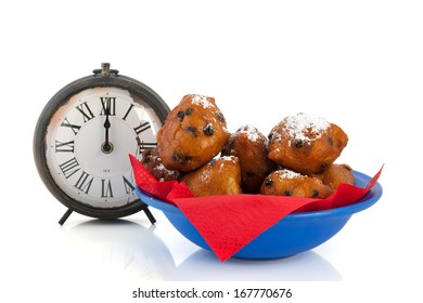 Dutch traditional oliebollen and watch on twelve o'clock isolated over white background