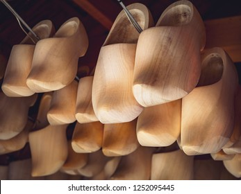 Dutch traditional wooden shoes closeup. Typical carved holland clogs - ancient farmer footwear and popular souvenir in tourist shops, symbol of the Netherlands.