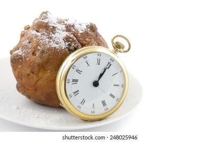 Dutch traditionally oliebol and pocket watch on twelve o'clock on New Years eve