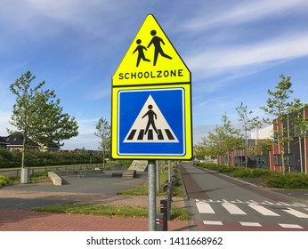 Dutch traffic road sign warning for a school zone and crosswalk.