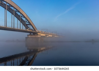 Dutch train coming out of the fog on the railroad bridge