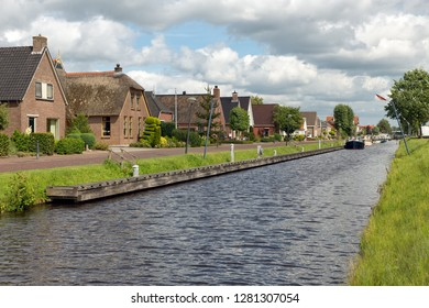Dutch village Appelscha in Friesland with houses along a canal and a beautiful cloudy sky