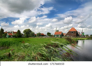 Dutch village Zaanse Schans in summer against a blue sky with clouds and green grass. Dutch mills