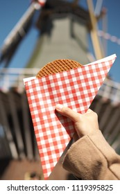Dutch Waffle or Stroopwaffle on wild mill background.