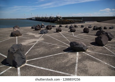 Dutch water management, Oosterschelde dam sea weir with free flow ability for ebb and flow, public art work with boulders and stripes in front