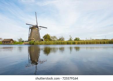 Dutch wind mill in polder landscape Kinderdijk, Unesco Heritage, against blue cloudy sky, Alblasserwaard, The Netherlands