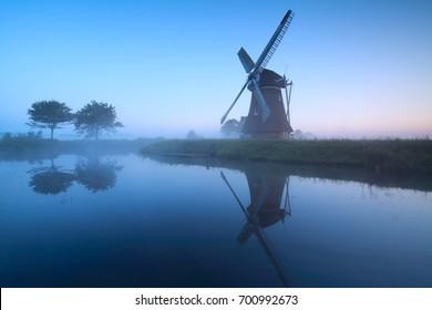 Dutch windmill by lake in dusk, Holland