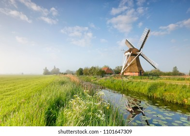 Dutch windmill by river over blue sky, Netherlands