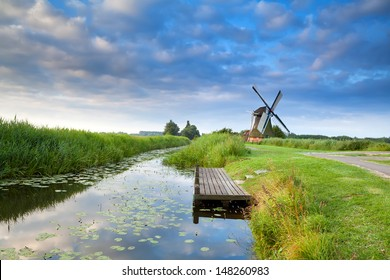 Dutch windmill by river with reflected blue sky, Groningen, Netherlands