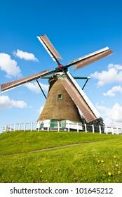 Dutch windmill in fresh green and blue sky