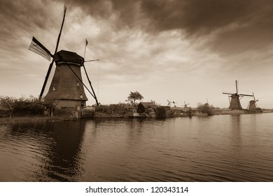 Dutch windmill. Reflection on water. River and gray sky.