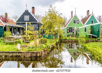 Dutch Windmill village Zaanse Schans Netherlands with beautiful historical houses and reflection in the water, green house at Zaandam