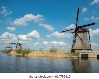 Dutch windmills along a river in Kinderdijk beautiful blue sky with clouds