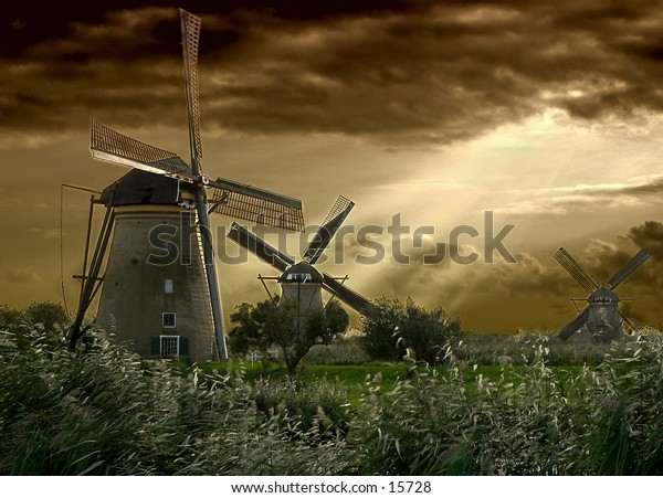Dutch windmills just after a storm, sun breaking trough the clouds. Filtered shot.
