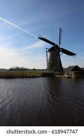 Dutch Windmills in Kinderdijk The Netherlands - Plane Line Connecting in Sky