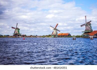 Dutch windmills in Zaandam with dramatic cloudy sky.