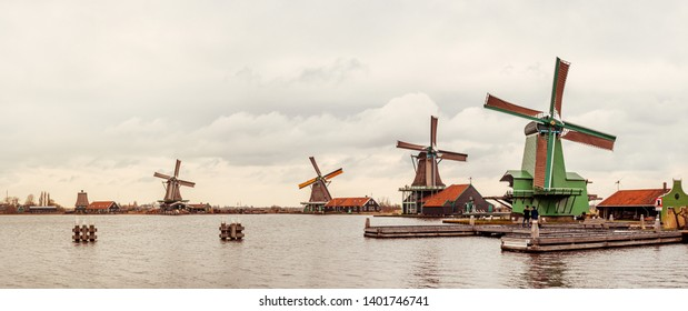 Dutch windmills in the Zaanse Schans village, near Amsterdam. Panoramic view with old wooden wind mills on the riverside - famous tourist landmarks and traditional rural landscape of the Netherlands.