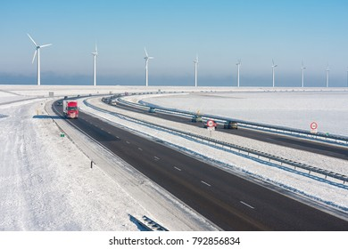 Dutch winter landscape with highway along wind turbines against a blue sky