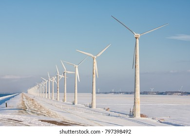 Dutch winter landscape with snowy fields and wind turbines aolong a dike