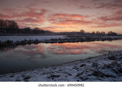 Dutch winter landscape at sunset reflected in the river