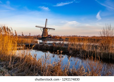 A Dutch Winter Wonder Land with a typical Holland Windmill in the rural area of the Netherlands on a cold but bright blue winter morning just after sunrise