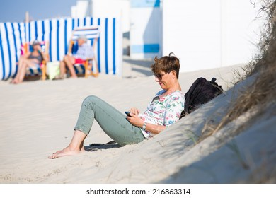 Dutch woman relaxing at the beach in Zeeland, Netherlands, on a bright summer day, looking at her smartphone and texting with her family