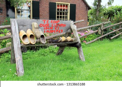 Dutch wooden shoes for sale on the side of a rural street in Holland. Text on wooden sign translation: 