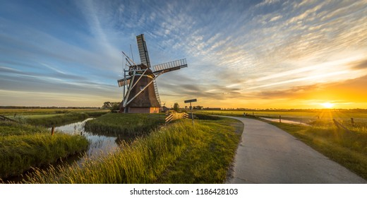 Dutch wooden windmill with cycling track at sunset in summer field with flowers and beautiful sky