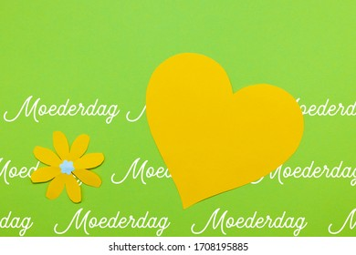 Dutch word Moederdag (Mothers day) with a yellow heart and a yellow paper flower on a green background. Room for copy.