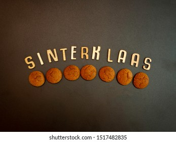 Dutch word Sinterklaas, meaning Saint Nicolas and cookies called pepernoten. Flay lay on a dark background with room for text.