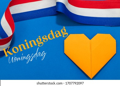 Dutch words Koningsdag (Kings day) and Woningsdag (House day) with a red white and blue ribbon and an orange paper heart on a blue background. Room for copy.