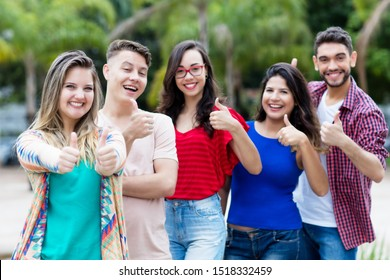 Dutch young adult woman with group of friends in line outdoor in the city in summer