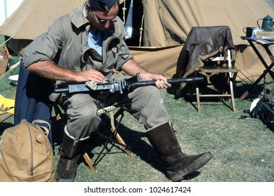 Duxford Aerodrome Essex England 2003. A reenactor wears the period uniform of a WW2 RAF armourer he sits cleaning a machine gun in front of a camp setting at a re-enactment event.