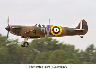 DUXFORD, CAMBRIDGESHIRE, UK - JULY 11, 2015: Supermarine Spitfire Mk. I QV- N3200 (G-CFGJ), 19 Sqn RAF, recovered from Sangatte beach in France, takes off out of Duxford during Flying Legends.