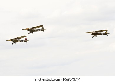 DUXFORD, CAMBRIDGESHIRE, UK - JULY 11, 2015: Pipers L-4A Cub 57-G (G-AKAZ), L-4H Grasshopper 329854 L  44-R (G-BMKC) and L-4B Cub 3681 (G-AXGP)  carry out a display at Duxford airfield.