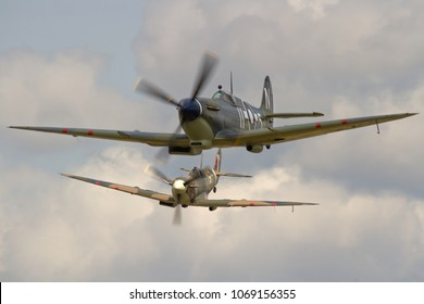 DUXFORD, CAMBRIDGESHIRE, UK - JULY 11, 2015: European camouflaged Supermarine Spitfire Mk Vb BM597 JH-C (G-MKVB) closes in on Asian Supermarine Spitfire Mk LF III PP972 (G-BUAR) during Flying Legends.