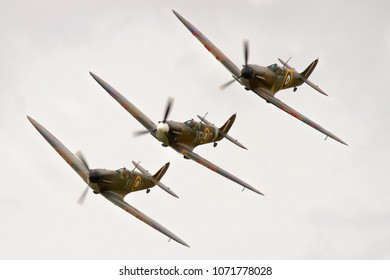 DUXFORD, CAMBRIDGESHIRE, UK - JULY 11, 2015: Supermarine Spitfires  Mk. I QV- N3200 (G-CFGJ), Mk. I X4650 KL-A (G-CGUK) and Mk. Ia P7308 XR-D (G-AIST) flying in formation during Flying Legends.