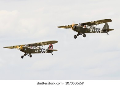 DUXFORD, CAMBRIDGESHIRE, UK - JULY 11, 2015: Piper L-4A Cub 57-G (G-AKAZ) and Piper L-4H Grasshopper 329854 L  44-R (G-BMKC)  carry out a display at Duxford airfield during Flying Legends.