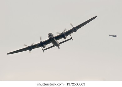DUXFORD, CAMBRIDGESHIRE, UK - SEPTEMBER 14, 2014: Canadian Warplane Heritage Museum's Avro Lancaster Mark X KB726 C-GVRA is escorted into Duxford airspace by a BBMF spitfire, and about to display.