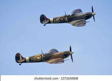 DUXFORD, CAMBRIDGESHIRE, UK - SEPTEMBER 14, 2014: Supermarine Spitfires Mk. Vb BM597 JH-C (G-MKVB) and Mk. Vb AE-A EP120 (G-LFVB) display together over Duxford airfield.