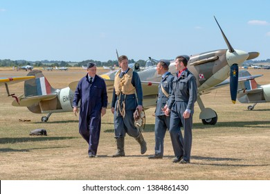 Duxford, Cambridgeshire/United Kingdom - 15/07/2018: A group of male RAF re-enactors walk past a parked Supermarine Spitfire at Duxford Flying Legends 2018