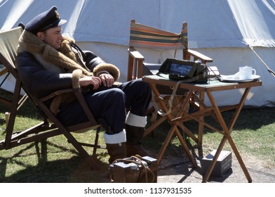 Duxford Essex UK 2003. An unidentified reenactor wears the period uniform of an RAF Pilot 1940 he sits on a deckchair at a re-enactment of the Battle of Britain.
