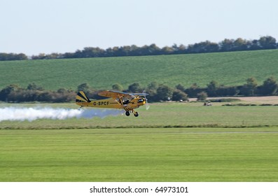 DUXFORD, UK - OCTOBER 10: Piper Cub flies extremely low during Autumn Air Show on October 10, 2010 in Duxford, UK