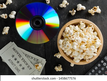 DVD or blu ray movie disc with tv remote control, movie tickets and bowl of popcorn on dark background. Home theatre movie or series night concept. Flat lay top view from above.