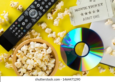 DVD or blu ray movie disc with tv remote control, movie tickets and bowl of popcorn on yellow background. Home theatre movie or series night concept. Flat lay top view from above.