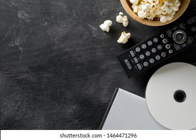 DVD or blu ray movie disc with tv remote control and bowl of popcorn on dark background. Home theatre movie or series night concept. Flat lay top view from above with copy space.