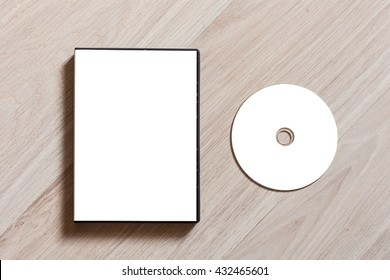 Dvd or cd disc cover case mockup. Template with plastic box and disc with white isolated free space for design. Mock up with black package for compact or dvd disc. On wooden table background