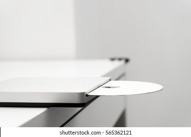 DVD drive/Clean composition with white office objects such as a DVD drive with a DVD half inserted on a white desk.