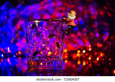 A dwarf or Santa Claus climbed on to a crystal ice bucket against a blue-violet bokeh background. Festive atmosphere, magic light, colorful bokeh in the form of asterisks.