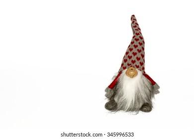 Dwarf toy on a white background. Souvenir toy leprechaun in the hood.